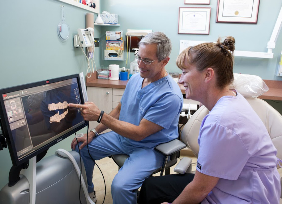 Dr. Brooks and dental team member looking at computer