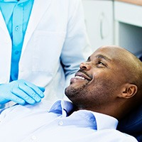 Man in dental chair smiling at dentist