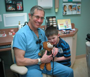 Dr. Brooks giving young child stuffed bear