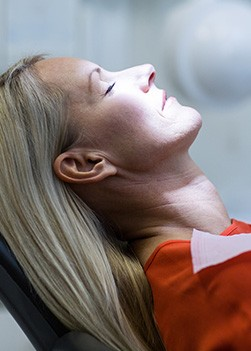Relaxing woman with eyes closed in dental chair