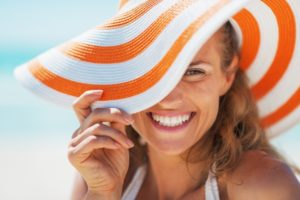 woman wearing a sunhat and following summer oral health tips